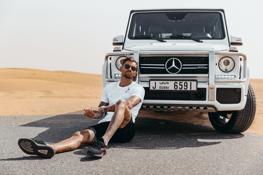 Model Wearing Marveli Men's Fashion T-Shirt Wings Printed White in Front of Mercedes-Benz G-Class SUV, Dubai
