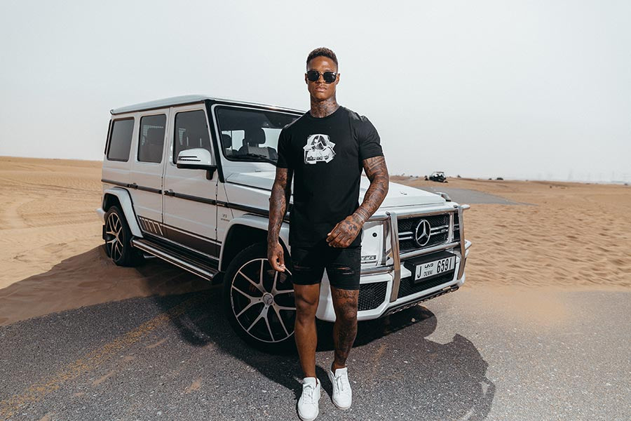 Marveli Men's Fashion in Dubai - Model Wearing Polaroid Blow Black Printed T-Shirt 2 on Mercedes-Benz SUV G-Class