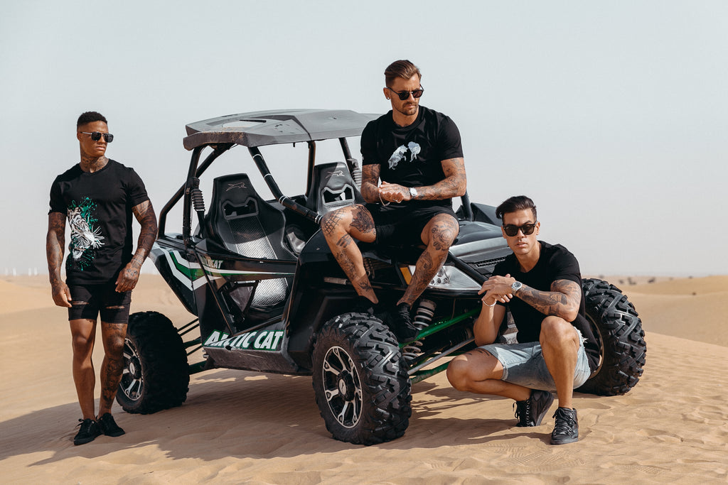 Marveli Men's Fashion in Dubai - Models Wearing Snow Wolves Black, LKDP and White Tiger Printed T-Shirts on Desert Buggy