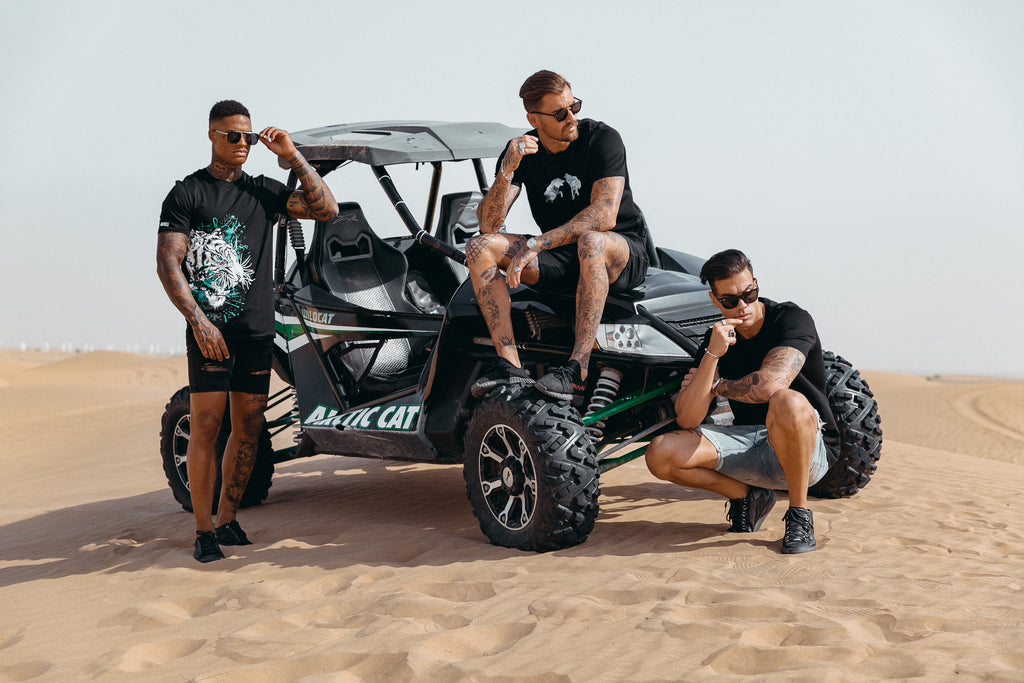 Marveli Men's Fashion in Dubai - Models Wearing Snow Wolves Black, LKDP and White Tiger Printed T-Shirts 2 on Desert Buggy