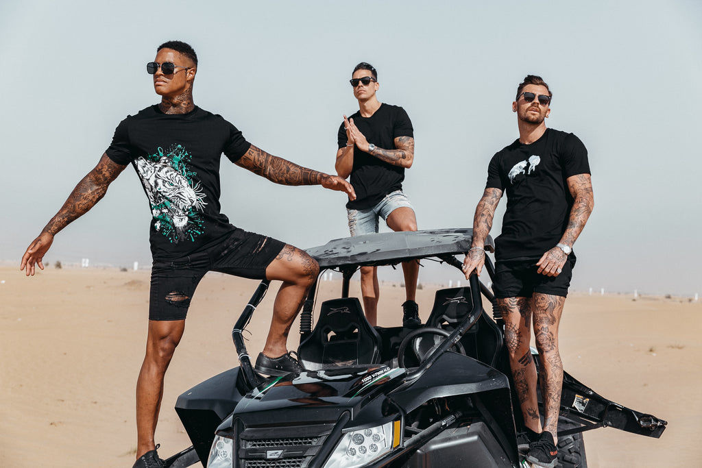 Marveli Men's Fashion in Dubai - Models Wearing Snow Wolves Black, LKDP and White Tiger Printed T-Shirts 4 on Desert Buggy