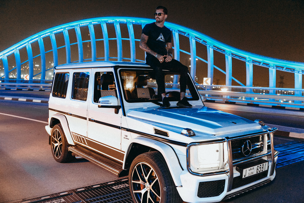 Marveli Men's Fashion in Dubai - Model Wearing Marveli Logo Navy Blue Printed T-Shirt on Bridge with Mercedes-Benz G-Class SUV