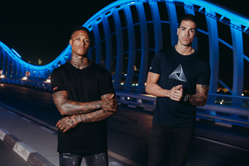 Marveli Men's Fashion in Dubai - Models Wearing LKDP Black and Marveli Logo Navy Blue Printed T-Shirts on Bridge