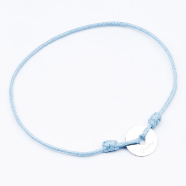 This bracelet is an ideal present for a newborn! 18kt White gold baby coin with blue thread.