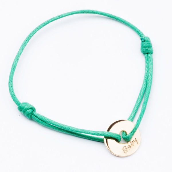 This bracelet is an ideal present for a newborn! 18kt Yellow gold baby coin with green thread.