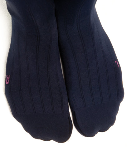 two feet wearing the Mediven for Men Classic compression socks show the anatomically cut foot portion and pinstripe design