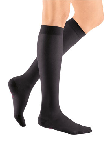 ladies legs wearing a pair of black colored Mediven Sheer & Soft knee high compression stockings