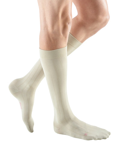 man wearing a pair of tan knee-high compression socks the Mediven for Men Classic sock has a thin verticle pinstripe design