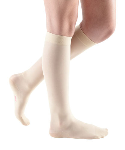 ladies legs wearing a pair of wheat colored Mediven Sheer & Soft knee high compression stockings