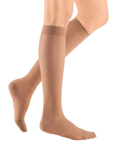 ladies legs wearing a pair of toffee colored Mediven Sheer & Soft compression stockings with closed toe