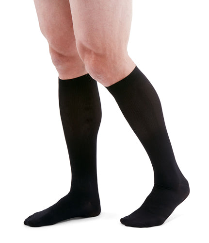 man wearing a pair of black knee-high compression socks the Mediven for Men Classic sock has a thin verticle pinstripe design