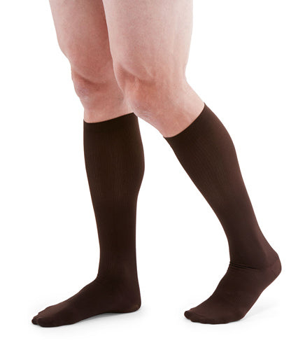 man wearing a pair of brown knee-high compression socks the Mediven for Men Classic sock has a thin verticle pinstripe design