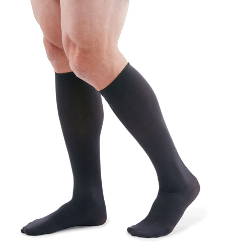 man wearing a pair of grey knee-high compression socks the Mediven for Men Classic sock has a thin verticle pinstripe design