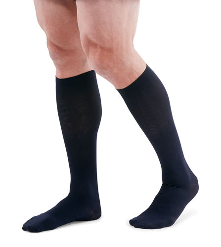 man wearing a pair of navy knee-high compression socks the Mediven for Men Classic sock has a thin verticle pinstripe design