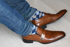 Multicolored argyle dress socks for men displayed inside black shoes
