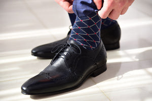 Blue dress socks for men with a colorful design matching black derby shoes
