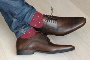 Man wearing burgundy socks with brown shoes and jeans