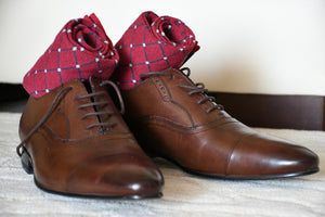 Colorful red socks for men with grey polka dots and brown oxford shoes