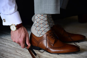 Man wearing unique and elegant dress socks with orange polka dots and matching accessories