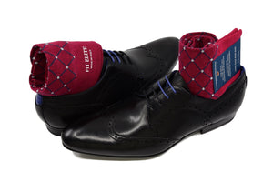 Men's colorful dress socks, red with grey polka dots, displayed inside black shoes