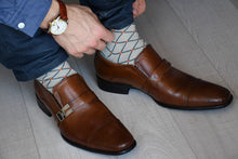 Man wearing luxury cotton socks, grey with orange polka dots matching brown shoes