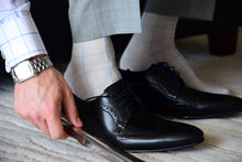 Elegant dress socks for men, light grey with blue checks, matching formal outfit
