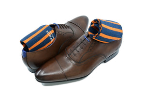 Men's colorful navy blue and orange striped dress socks with brown shoes