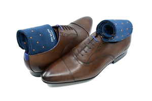 Men's navy blue dress socks with orange polka dots by Fit Elite displayed inside brown dress shoes