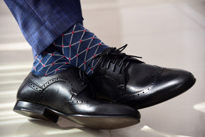 Men's navy dress socks patterned with red polka dots, matching navy blue pants