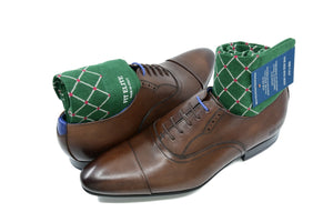Men's colorful dress socks, green with red dots, inside brown shoes