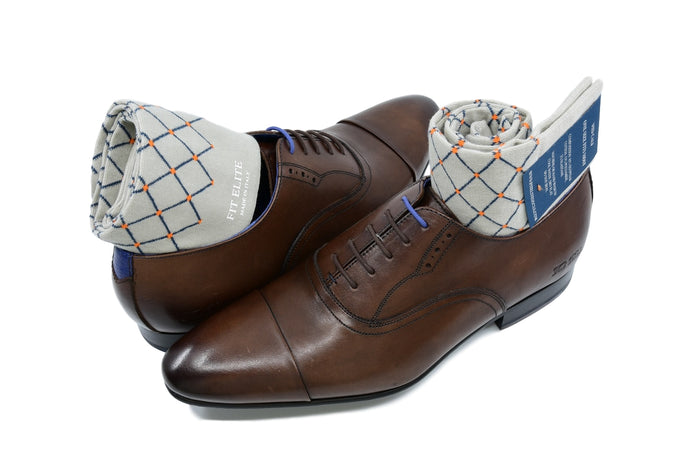 Men's patterned dress socks, grey with orange polka dots, displayed inside brown shoes