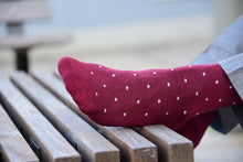 Man wearing burgundy polka dot socks with matching grey trousers