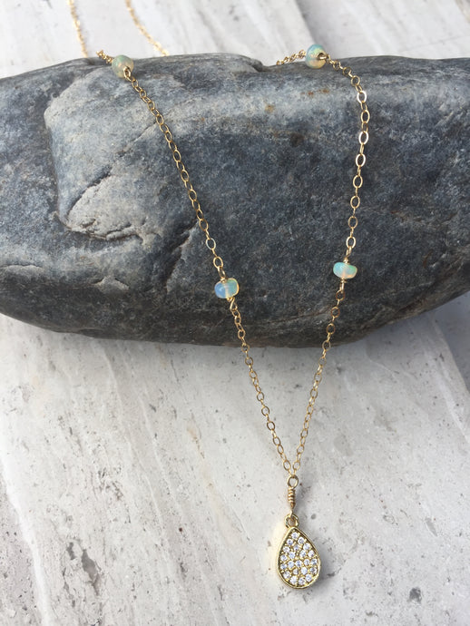 Opal and CZ Drop Necklace on rock