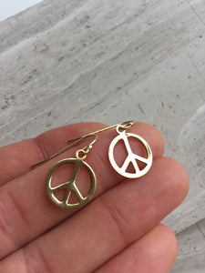 Peace sign earrings, gold, in hand