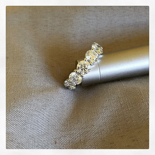 Custom eternity ring with 7.24 cttw of GIA certified round brilliant cut diamonds.