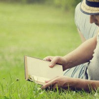 man_reading_book_sunny_day_grass_warm_relax_pic