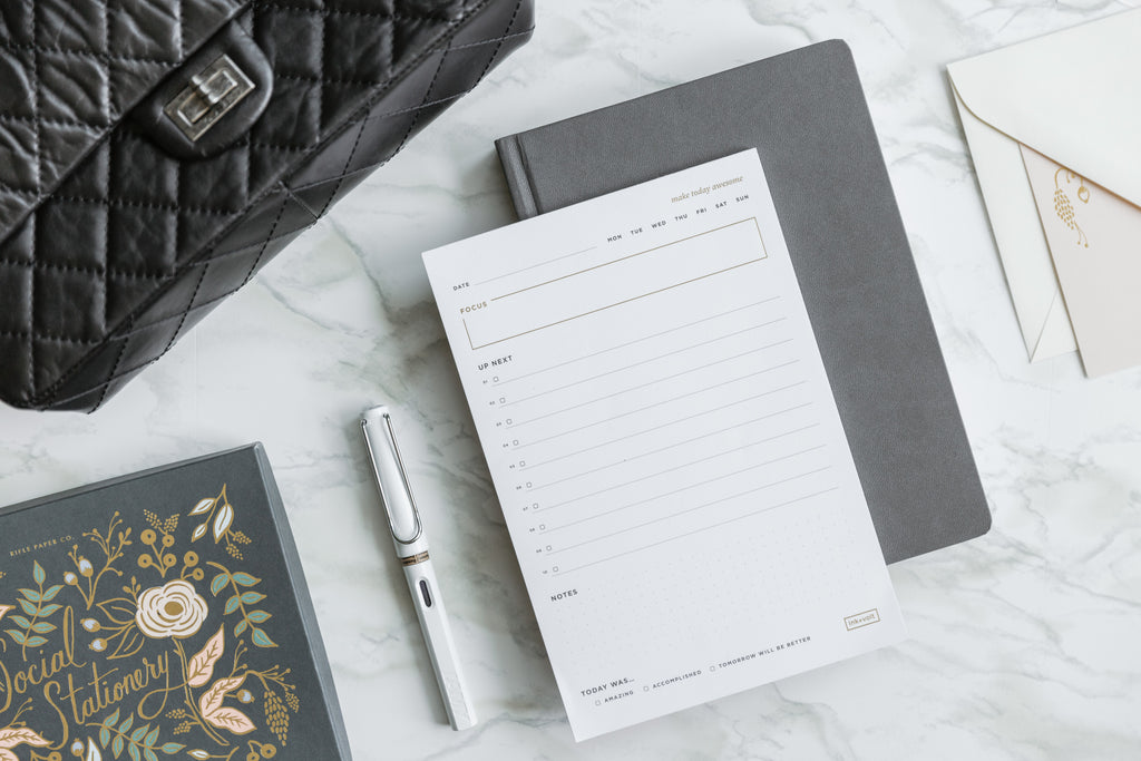 A grey Ink+Volt Planner on a marble countertop with a Daily Task Pad, Lamy Fountain Pen, and greeting cards.