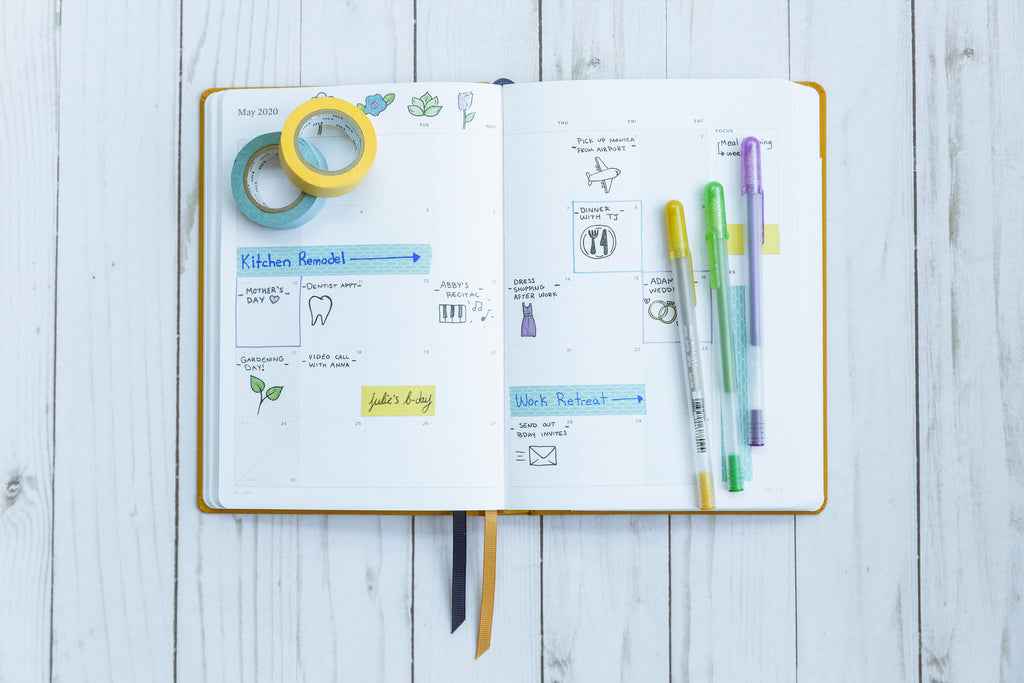 A goldenrod Ink+Volt planner sits on a wooden plank table with gel pens and washi tape on top.