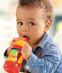 Young toddler drinking from a sippy cup with an AlergyAlert label