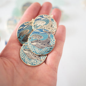 whale enamel pin in hand
