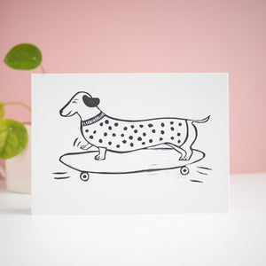 sausage roll sausage dog on a skateboard lino print card