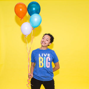 "Teenage girl wearing a blue t-shirt with ""Live Big"" in white and multi-color print"
