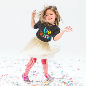 "Young girl wearing a dark grey/black long sleeve shirt with ""Be Kind"" on it in multi-color print"