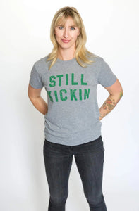Woman wearing a grey t-shirt with Still Kickin in green print