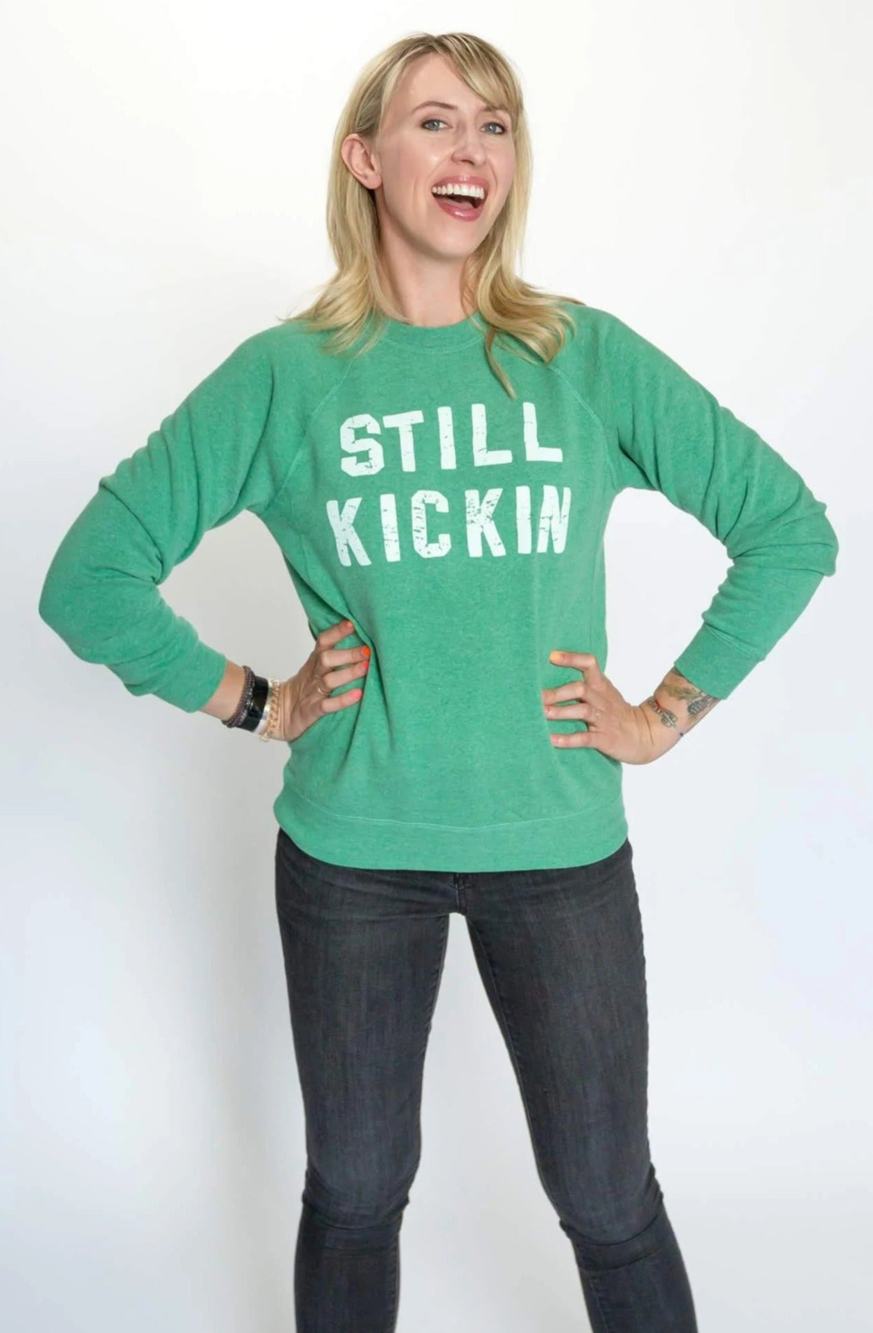 Nora McInerny wearing a green crewneck sweatshirt with Still Kickin printed in white print