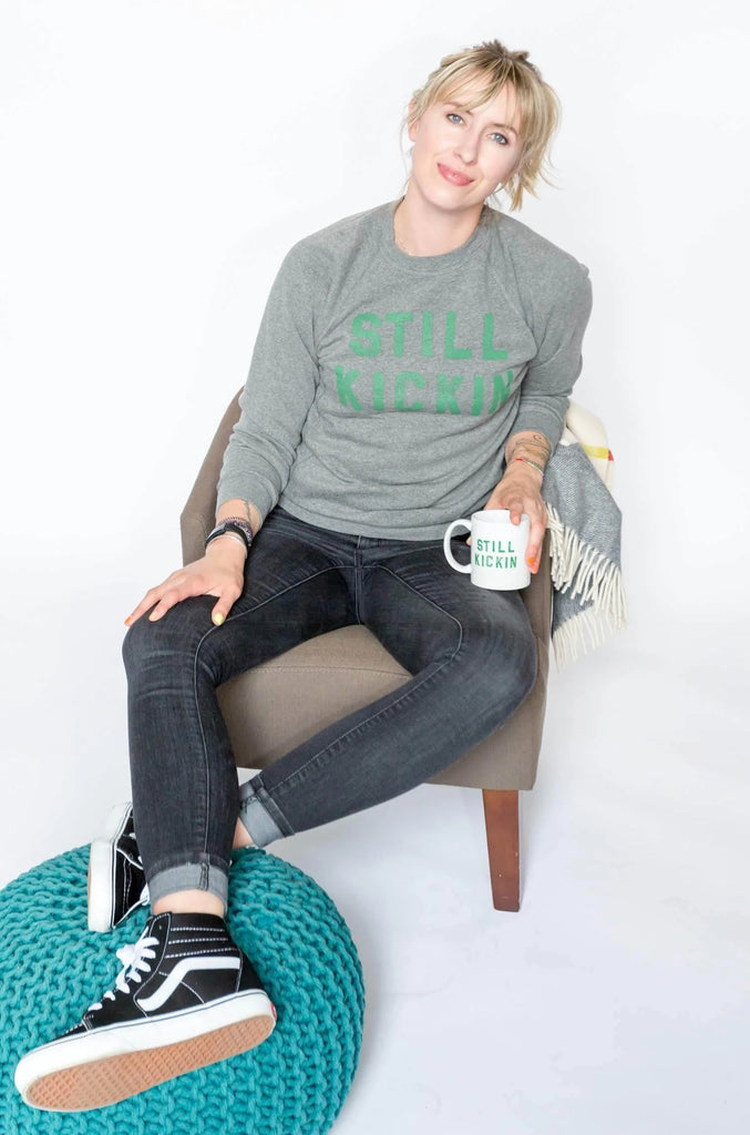 Nora McInerny wearing a grey crewneck sweatshirt with Still Kickin in green print