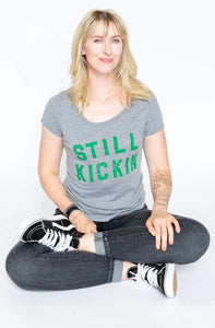 Nora McInerny wearing a grey t-shirt with Still Kickin in green print