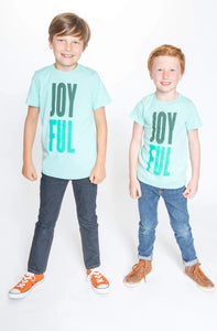 Two young boys wearing mint-colored t-shirts with JOY and FUL in forest green and dark mint print