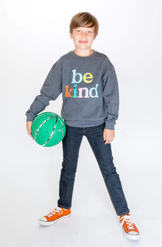 Young boy wearing a black heather crewneck sweatshirt with Be Kind in multi-colored print