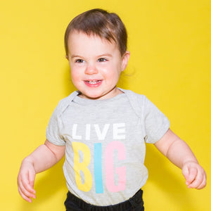 "Toddler wearing a light grey onesie with ""Live Big"" in white and multicolor print"